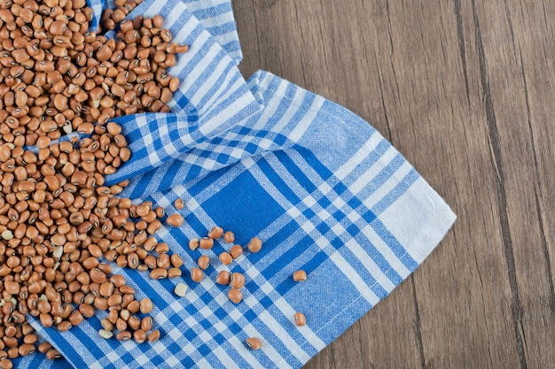 Haricots bruns crus sur table en bois.