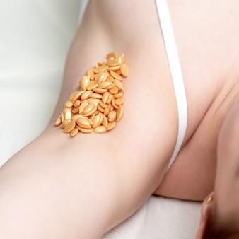 Haricots de cire sur l'aisselle de la femme