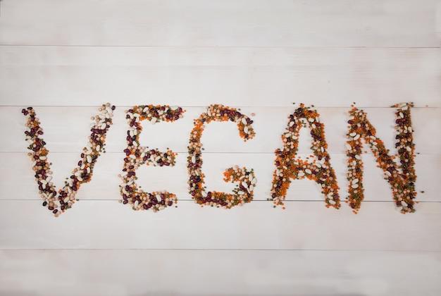 Haricots, lentilles, haricot mungo, pois disposés sur un fond en bois blanc sous la forme de l'inscription vegan