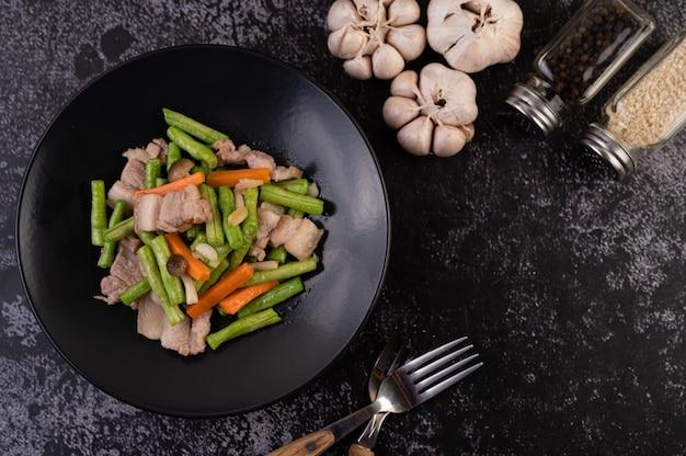 Les haricots longs et les carottes sautés, ajouter la poitrine de porc, mettre sur une assiette noire.