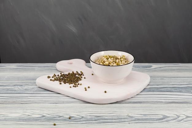 Haricots mungo germés dans un bol blanc sur une table en bois clair.