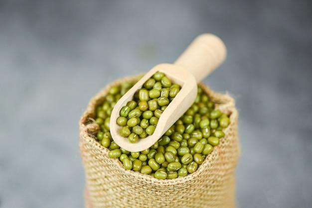 Haricots mungo verts dans le sac avec une cuillère en bois - grains de céréales de haricot mungo à grains entiers