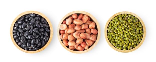 Haricots noirs, arachides, haricots mungo dans un bol en bois isolé sur fond blanc. vue de dessus