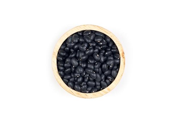 Haricots noirs sains dans une tasse en bois sur fond blanc