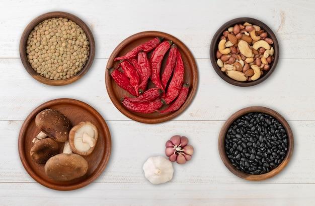 Haricots, noix, piments, champignons et ail sur une table en bois.