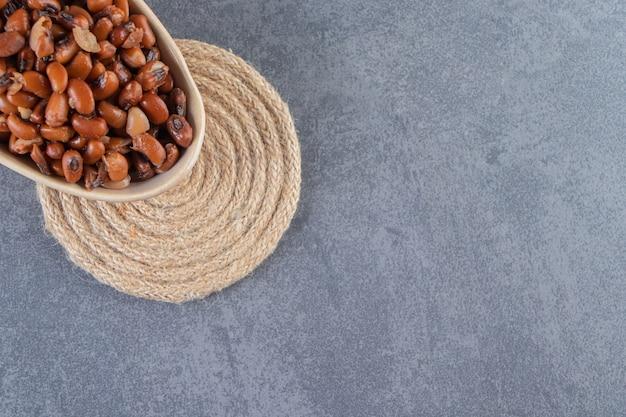 Haricots non cuits avec de la laitue dans un bol sur un dessous de plat, sur le fond de marbre.