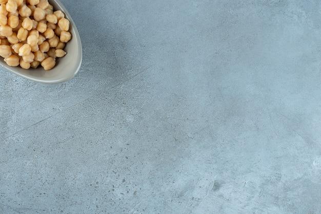 Haricots pois bouillis dans une tasse sur fond bleu. photo de haute qualité