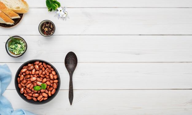 Haricots rouges bouillis décorés de feuilles de basilic dans un bol noir