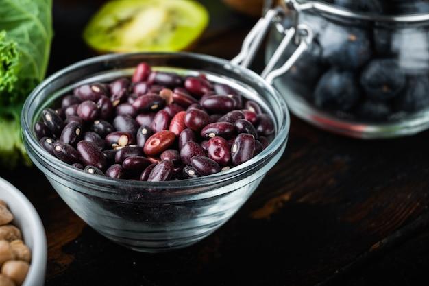 Haricots rouges dans un bol avec des ingrédients sains sur fond de bois foncé
