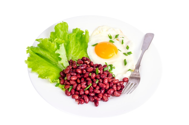 Haricots rouges, laitue et oeuf au plat pour le petit déjeuner.