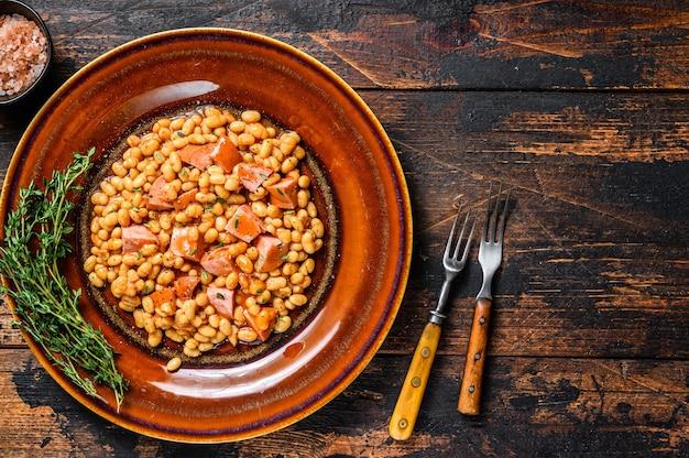 Haricots rouges avec saucisse fumée et sauce tomate dans une assiette. table en bois sombre. vue de dessus.