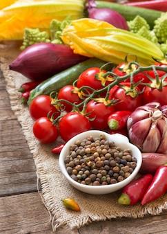 Haricots roveja biologiques crus dans un bol avec des légumes crus sur une table en bois se bouchent