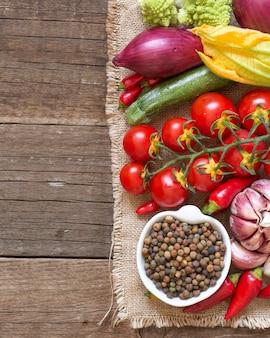 Haricots roveja biologiques crus dans un bol avec des légumes crus sur une vue de dessus de table en bois avec copie espace