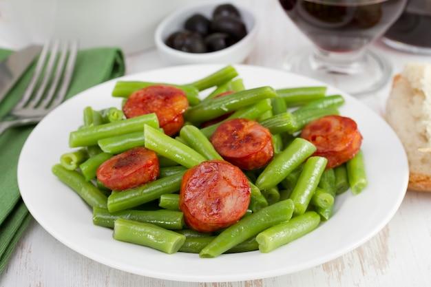 Haricots verts bouillis avec du chorizo dans l'assiette