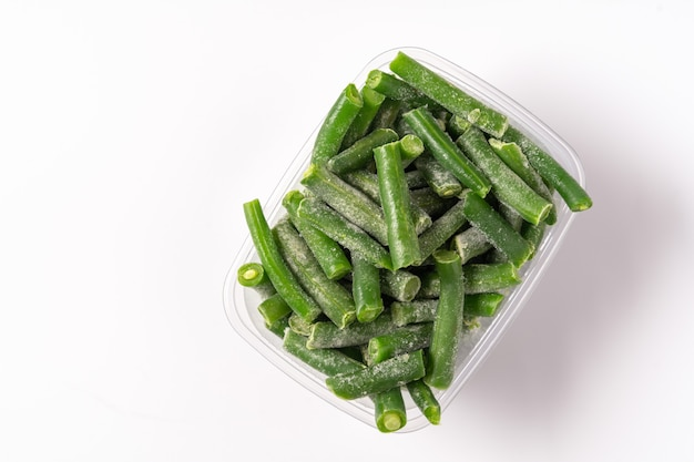 Haricots verts congelés dans une boîte en plastique isolé sur fond blanc, mise à plat.