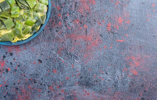 Haricots verts cuits avec oeuf dans une casserole.