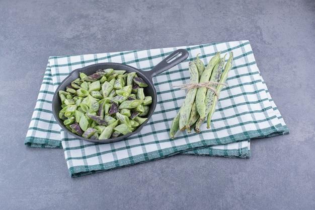 Haricots verts hachés dans une casserole sur une surface bleue