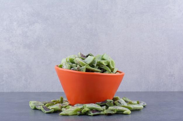 Haricots verts hachés à l'intérieur d'une tasse sur une surface bleue