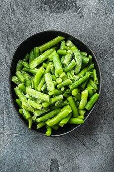 Haricots verts. haricots frais congelés pour salade, cuisine ou ensemble d'aliments végétaliens crus, dans un bol, sur pierre grise