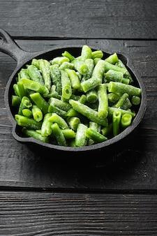 Haricots verts. haricots frais congelés pour salade, cuisine ou ensemble d'aliments végétaliens crus, dans une poêle en fonte, sur une table en bois noir