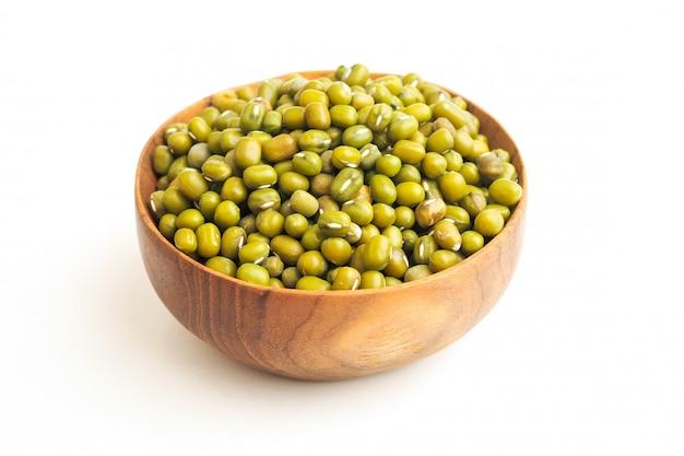 Haricots verts ou haricots mungo dans un bol en bois sur fond blanc