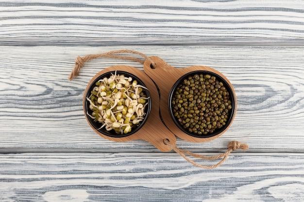 Haricots verts, haricots mungo germés sur fond de bois clair.