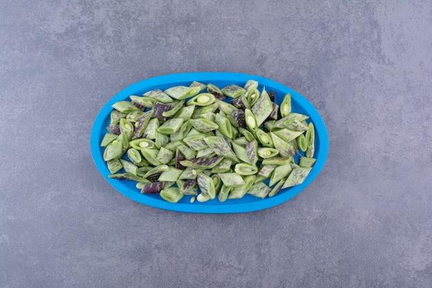 Haricots verts à l'intérieur d'un récipient ou d'un plateau sur fond de béton.