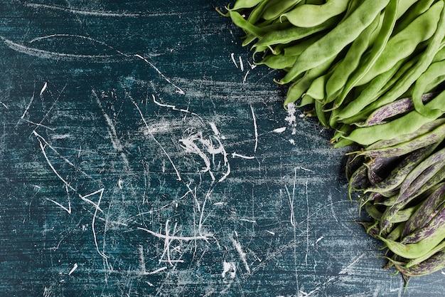 Haricots verts isolés sur tableau bleu.