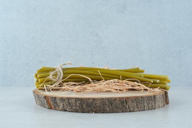 Haricots verts marinés sur morceau de bois.