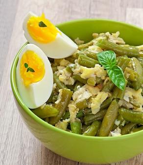 Haricots verts avec des œufs dans un bol.