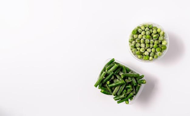 Haricots verts et pois surgelés dans une boîte en plastique isolé sur fond blanc, mise à plat.