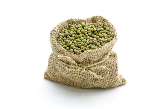 Haricots verts en sac, isolés sur une surface blanche