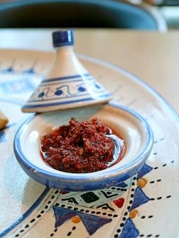 Harissa marocaine dans une mini casserole de tajine servie avec un plat marocain