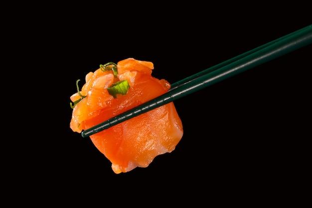 Hashi tenir des sushis et des rouleaux isolés sur fond noir
