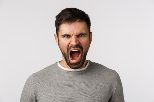 Hâte et énervé en colère criant un homme barbu avec une grimace effrayante, fronçant les sourcils mépris et mépris express, se plaignant de colère, hurlant furieusement