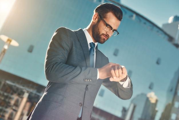 À la hâte, jeune et bel homme d'affaires barbu à lunettes et costume complet vérifiant le