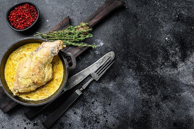 Haunches de lièvre cuit au four dans la casserole avec des légumes cuits. fond noir