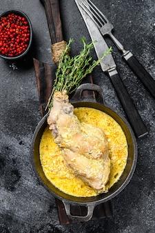Haunches de lièvre cuit au four dans la casserole avec des légumes cuits. vue de dessus.