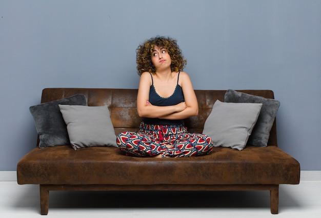 Haussant les épaules, se sentant confus et incertain, doutant avec les bras croisés et regard perplexe