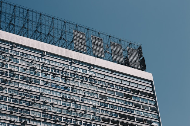 Haut d'un ancien immeuble d'appartements avec des projectiles métalliques sur le toit et ciel bleu clair