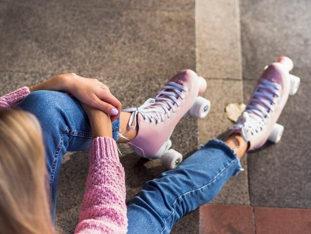 Haut angle de femme en jeans avec patins à roulettes