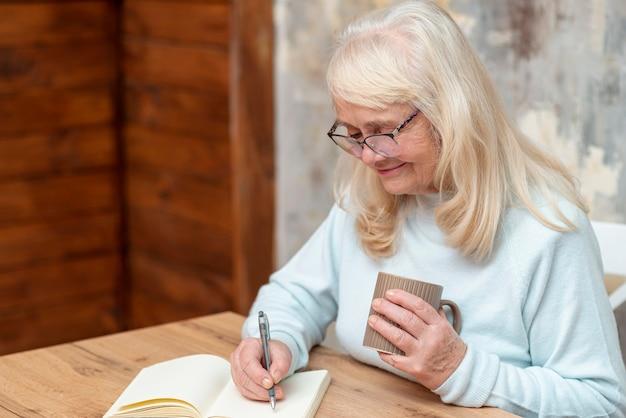 Haut angle femme senior écrivant à l'ordre du jour