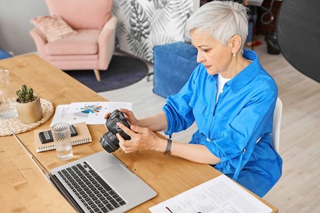 Haut angle de vue de l'élégante femme photographe d'âge moyen assis sur son lieu de travail avec un ordinateur portable ouvert, tenant un appareil photo reflex numérique sélectionnant les meilleurs clichés pour la retouche, ayant concentré l'expression concentrée