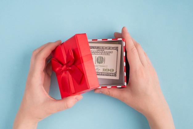 Haut au-dessus des frais généraux gros plan vue à la première personne photo de mains féminines boîte ouverte avec 100 billets américains isolés sur fond de couleur bleu pâte