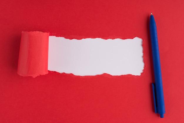 Haut au-dessus des frais généraux vue mise à plat photo de stylo à bille bleu papier rouge déchiré sur fond blanc avec copyspace