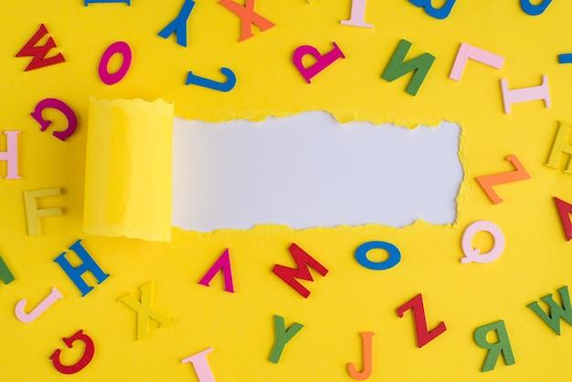 En haut au-dessus de la photo vue de dessus de lettres colorées et de papier jaune vif déchiré sur fond blanc avec fond