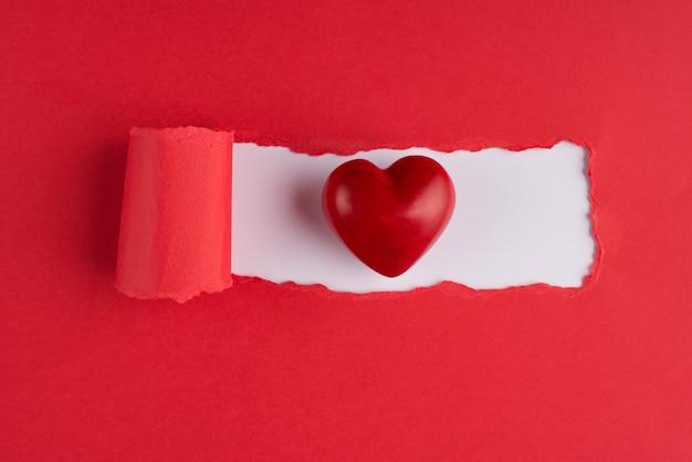 Haut au-dessus de vue aérienne photo d'un coeur rouge sur papier rouge déchiré sur fond blanc avec copyspace