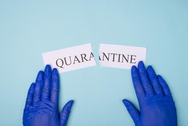 Haut au-dessus de la vue aérienne photo de mains dans des gants placés sur les côtés du mot de quarantaine isolé sur fond bleu
