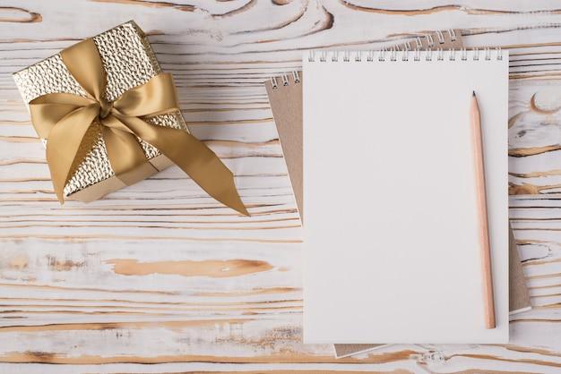 En haut au-dessus de la vue aérienne, photo à plat d'un crayon pour ordinateur portable vierge et d'une boîte cadeau dorée isolée sur fond de bois clair avec fond