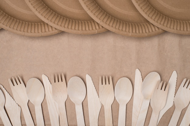 En haut au-dessus de la vue aérienne photo de rangées de couverts en bois et d'assiettes en papier isolées sur une table d'arrière-plan en papier craft
